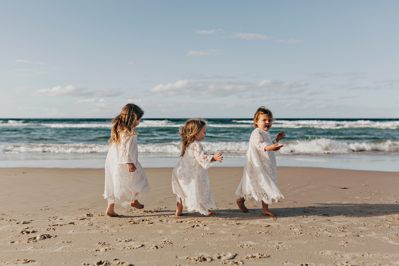 Flowergirls play at beach in boho relaxed Byron wedding.