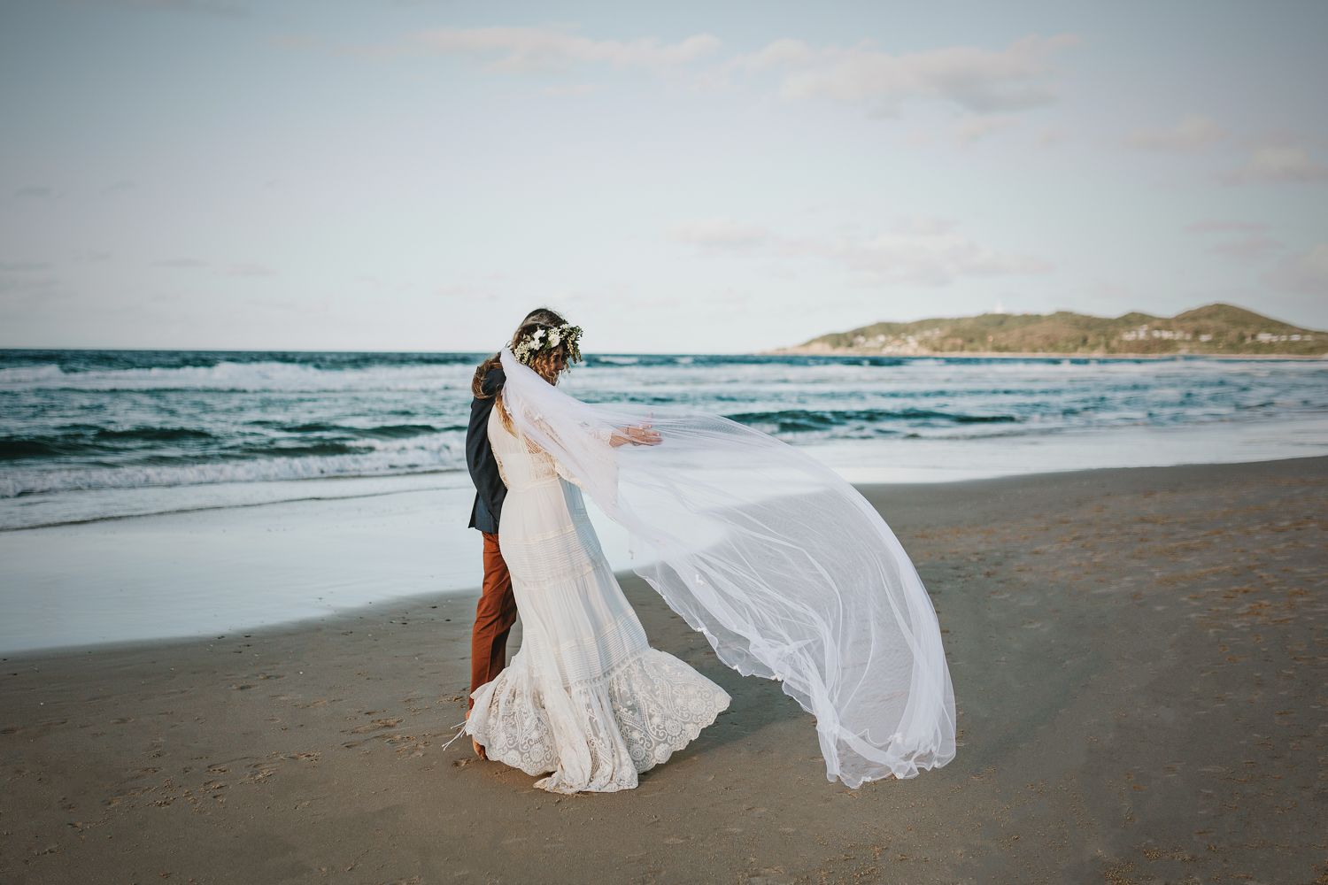 Bride and groom walk with veil blowing in breeze.