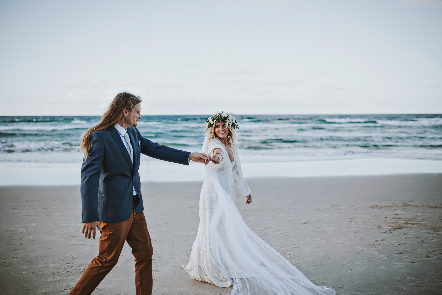 Bride smiles at her groom after their wedding at the beach.