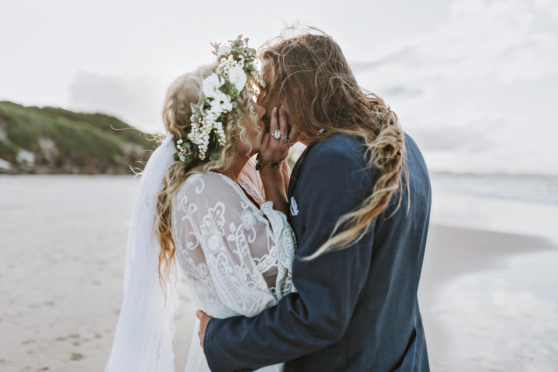 Bride and groom kiss on the beach in boho wedding.