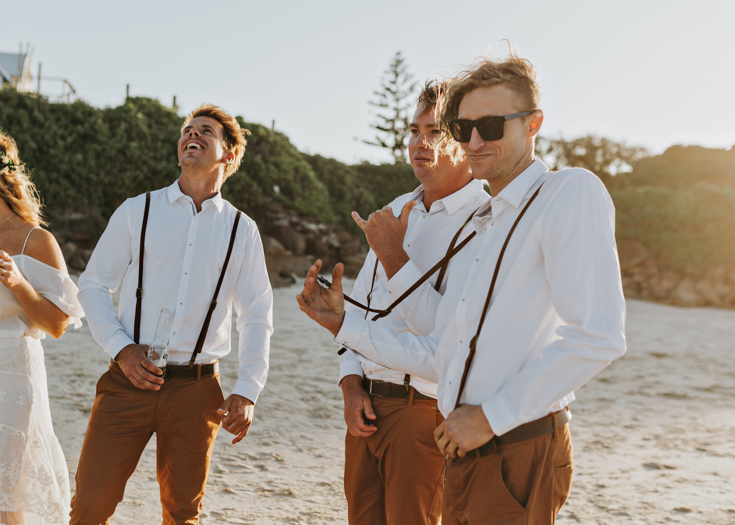 Groomsmen relax after barefoot wedding ceremony in Byron Bay.
