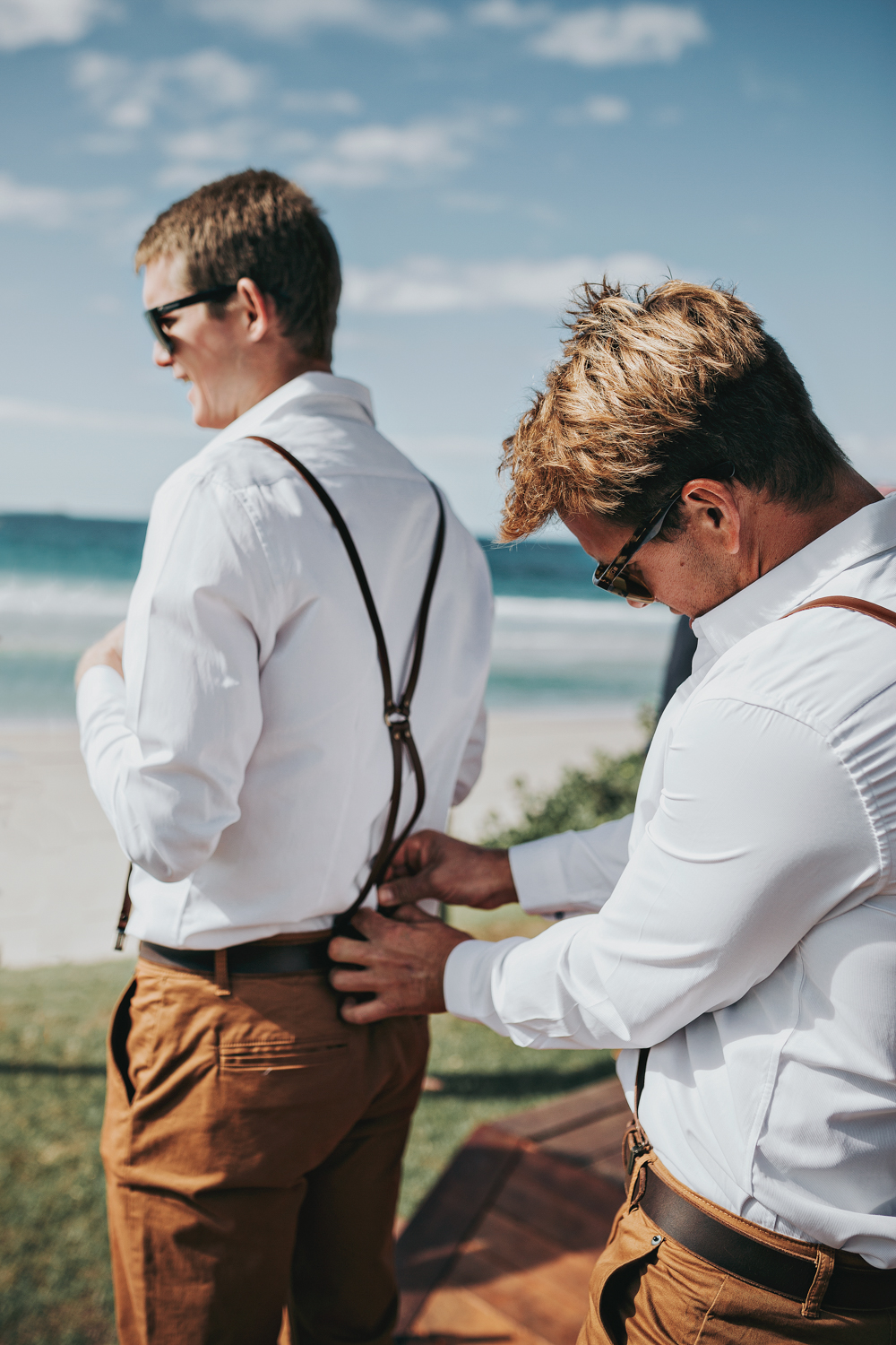 Groomsman assists with getting ready for wedding ceremony in Byr