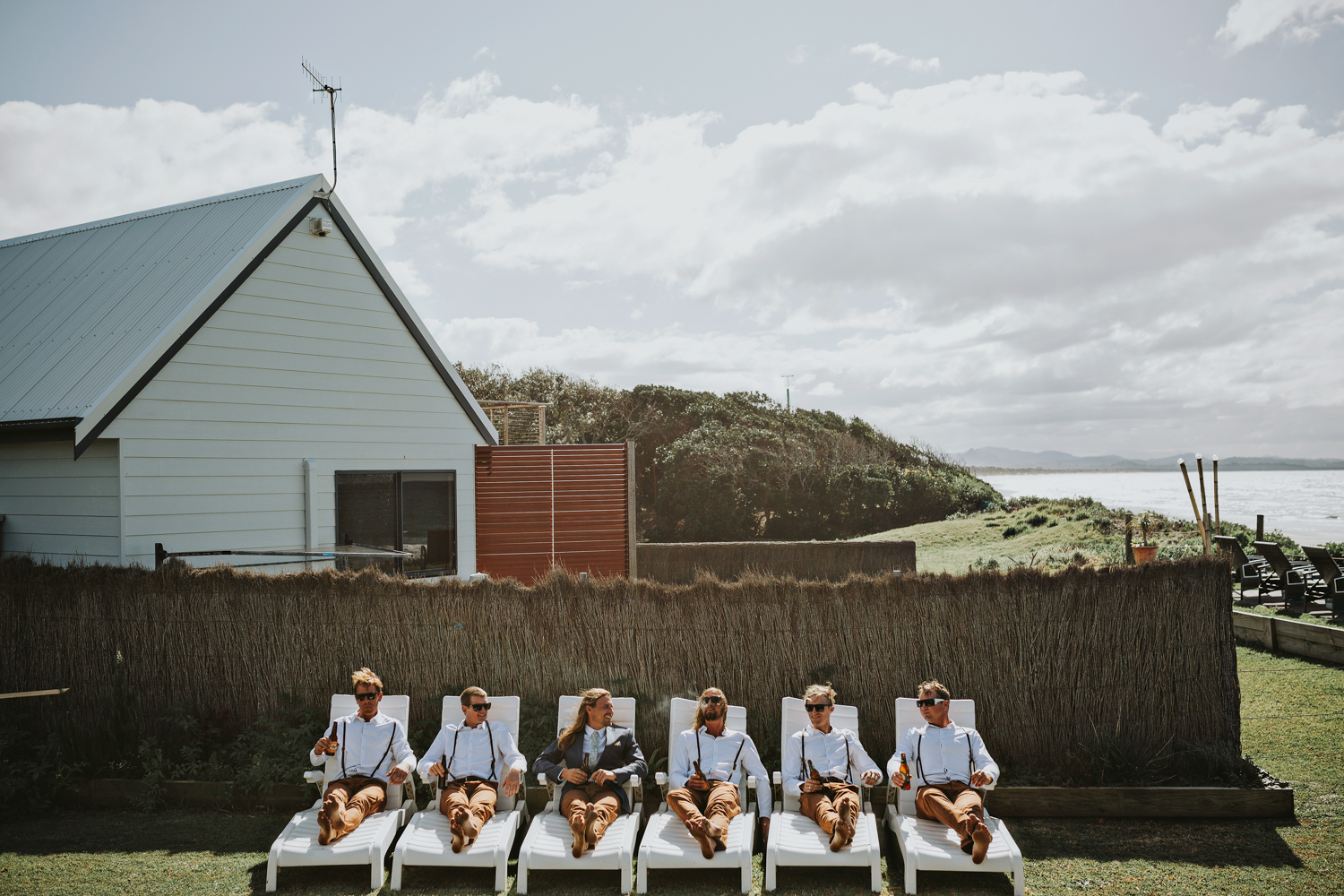 Groomsmen relax before barefoot wedding ceremony in Byron Bay.