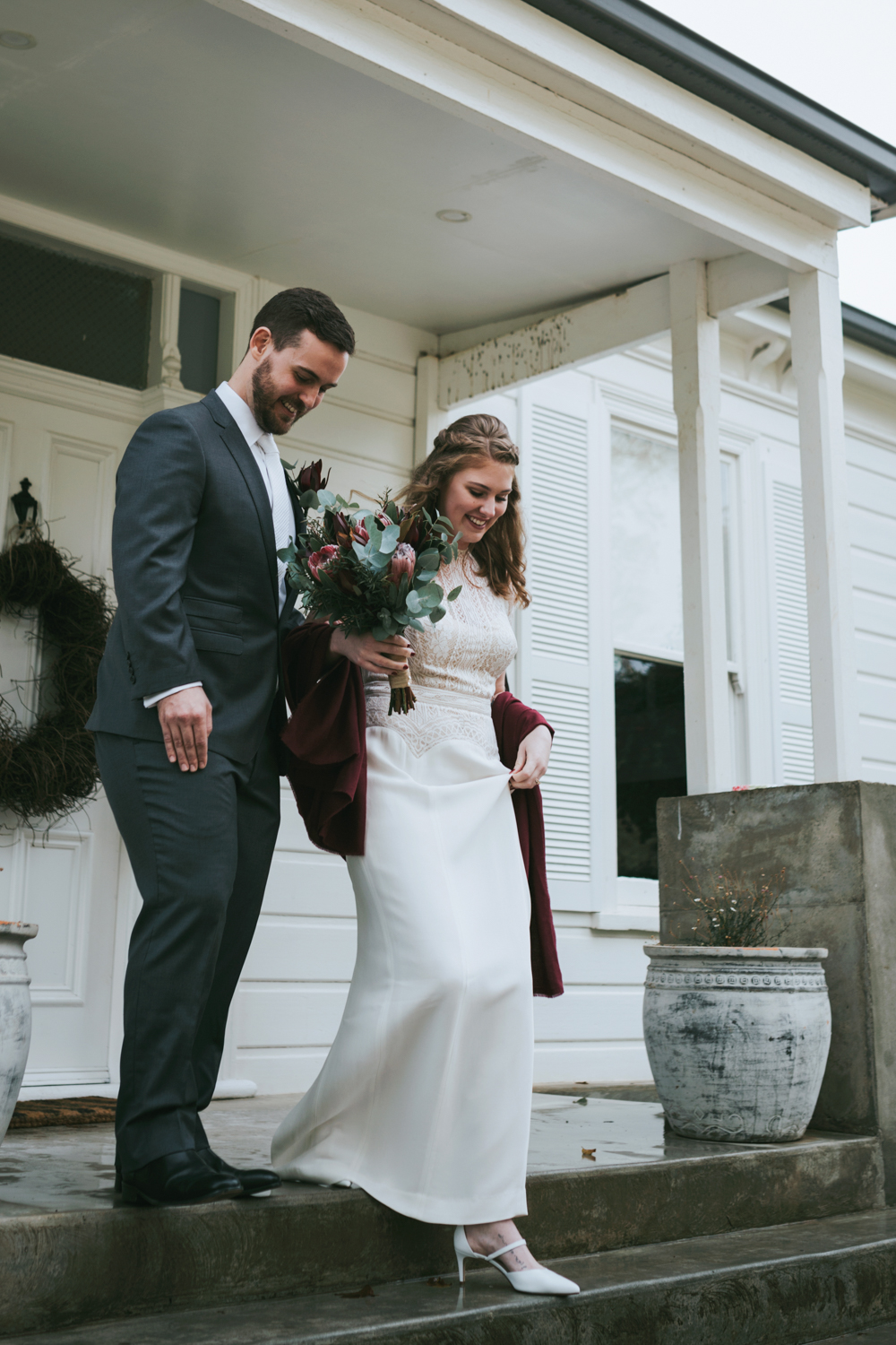 Bride and groom walk down stairs after marrying.