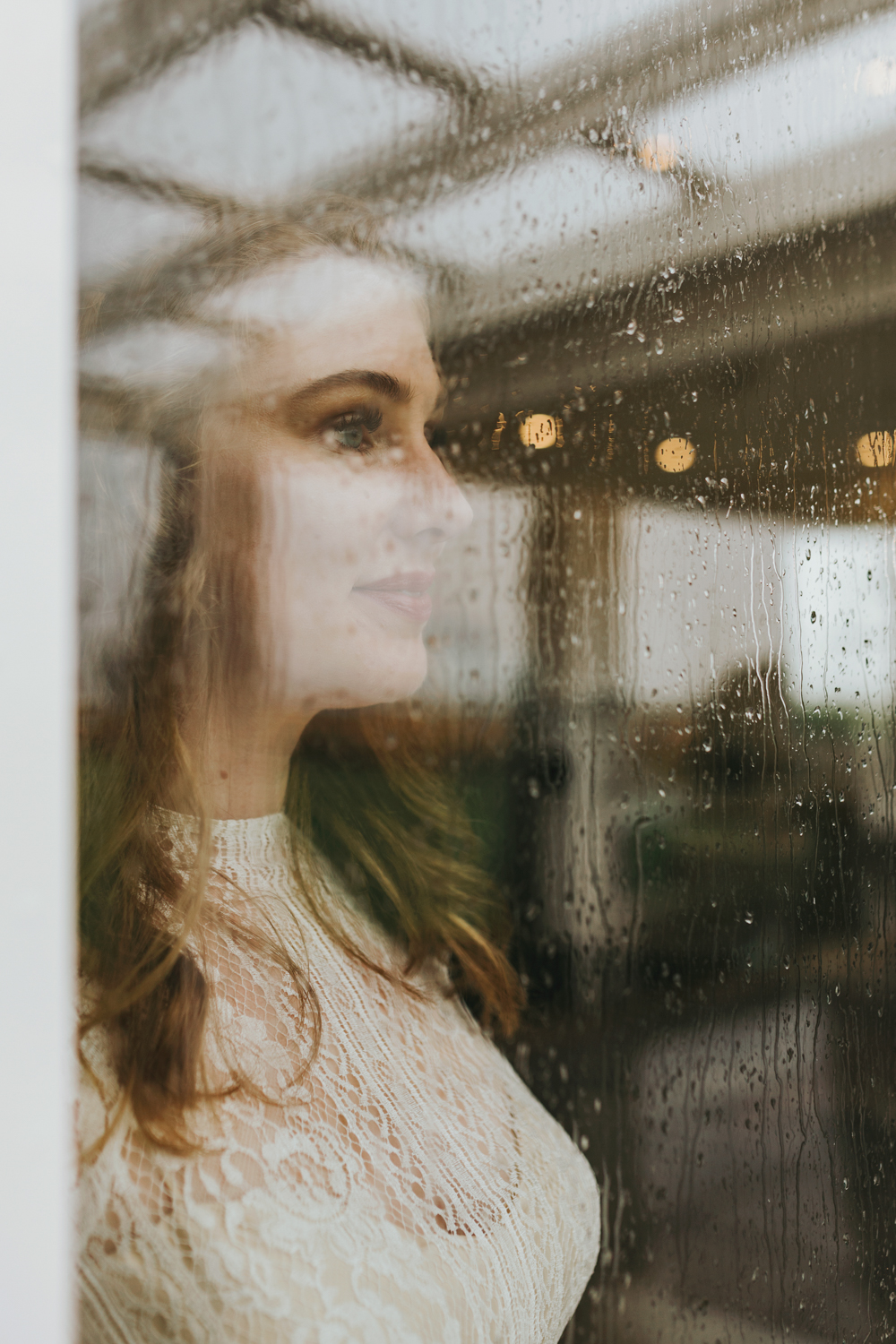 Bride looks out to rainy day on her wedding day.