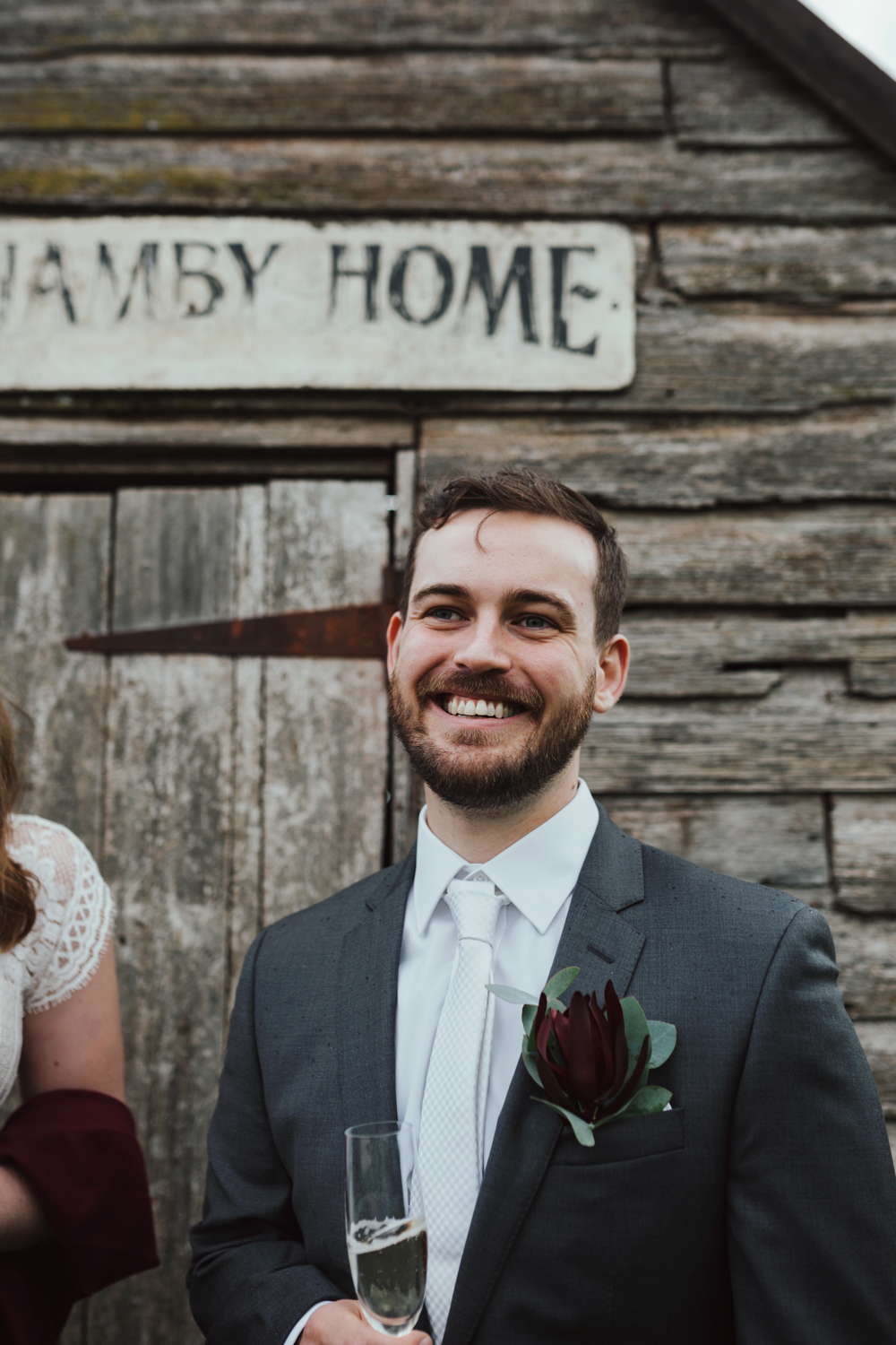 Groom smiles with champagne glass at Quamby House in Tasmania.