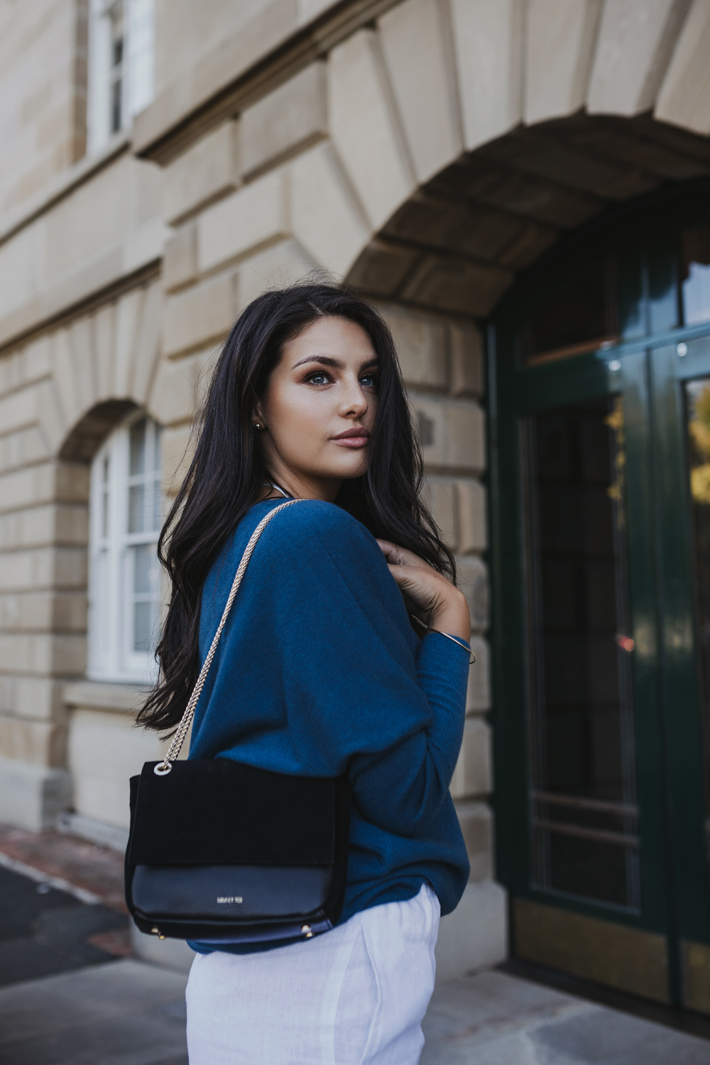 model holds black leather bag from fashion store in Hobart.
