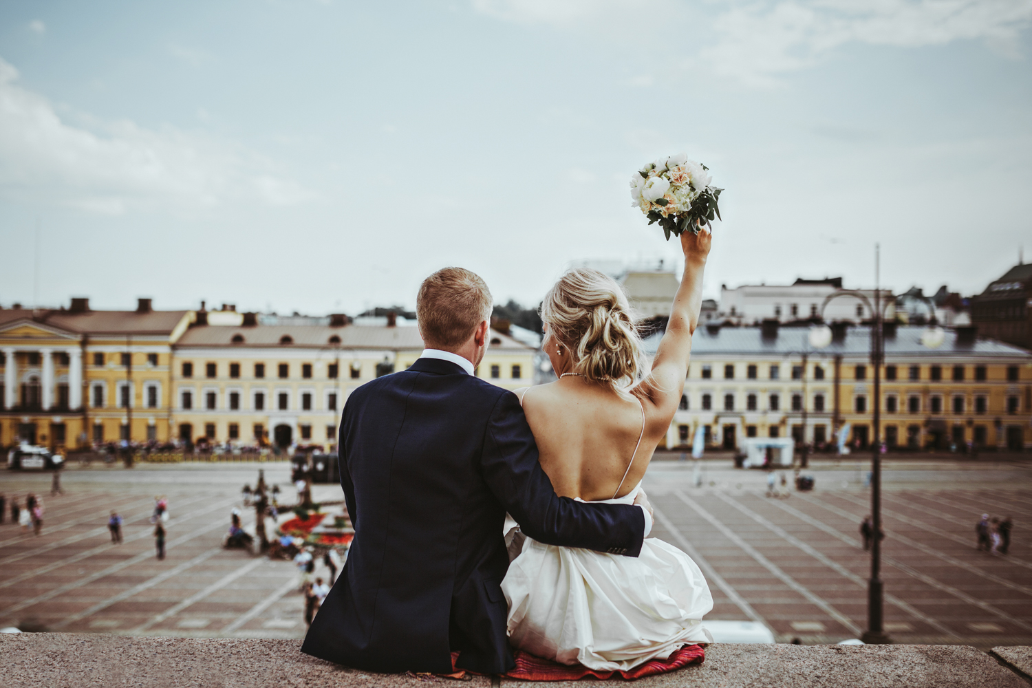 Bride hold bouquet in the air at wedding in Helsinki Finland.