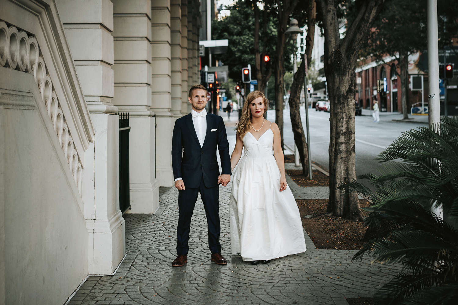 Bride and groom stand holding hands in city after wedding.
