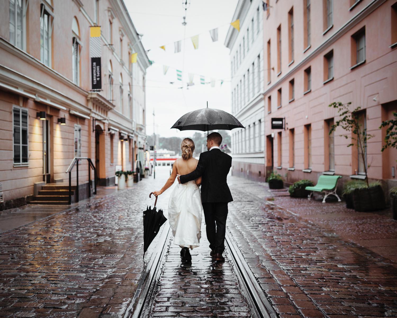 Newlyweds walk down rainy cobblestone street in Finland.