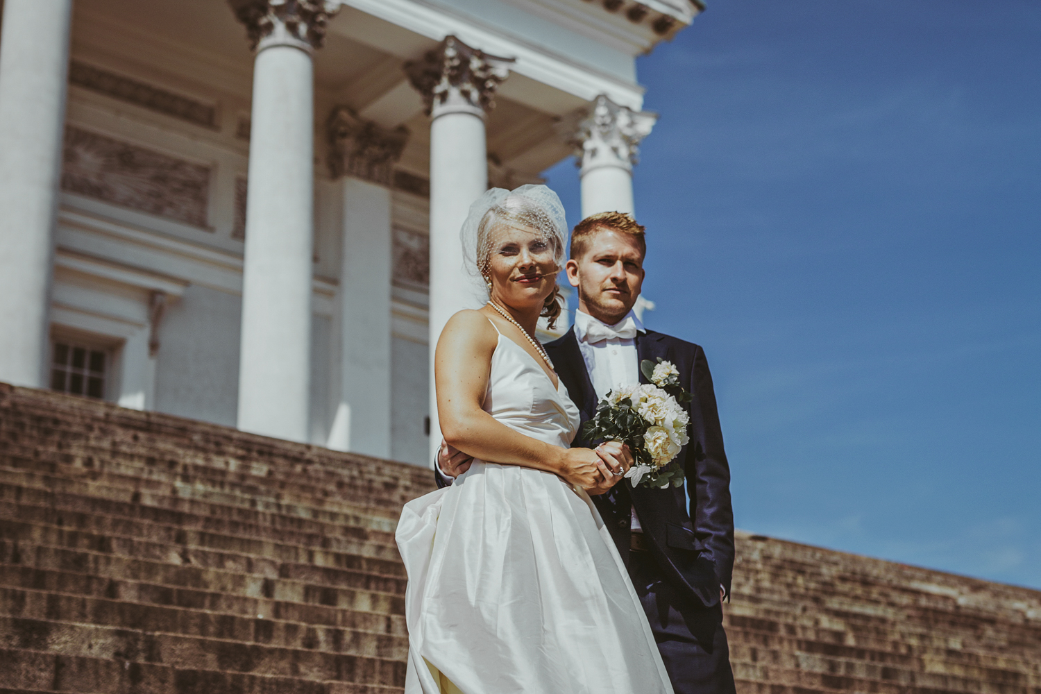Bride and groom stand on steps in Cathedral Square in Helsinki F