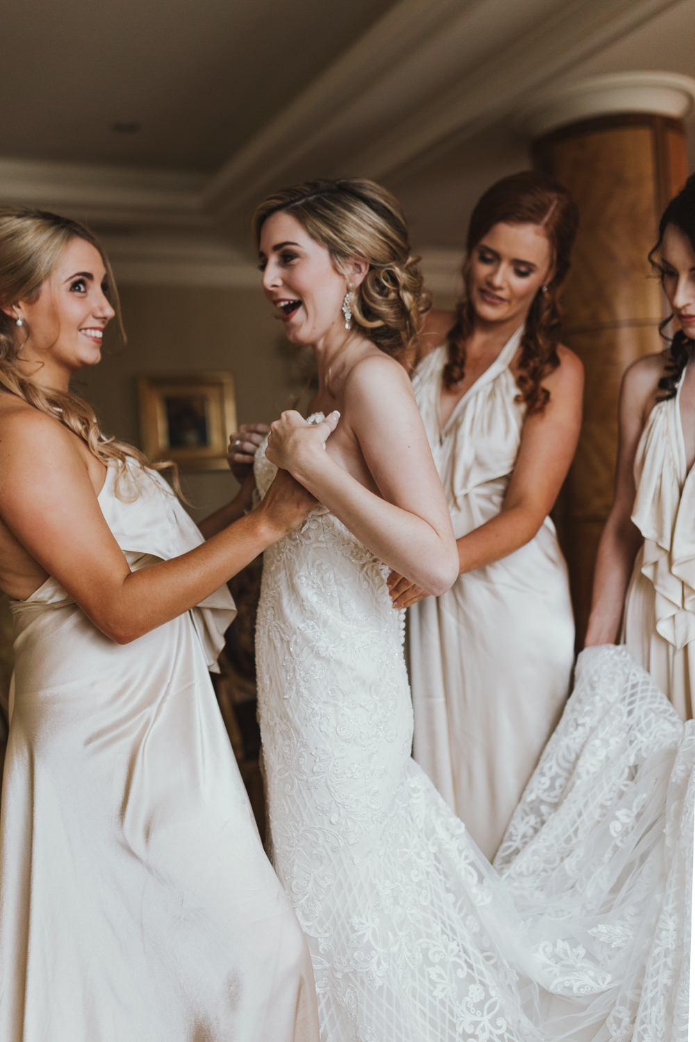Bridesmaid assists bride and smiles at wedding in Brisbane.