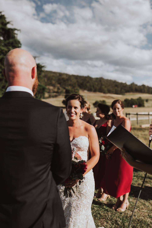 Bride smiles at her groom during wedding ceremony in Tasmania.