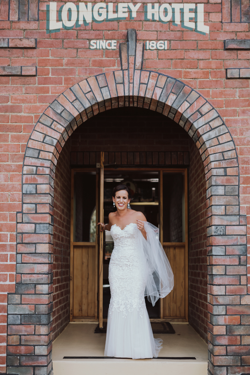 Bride walks out of Longley Hotel in wedding gown.