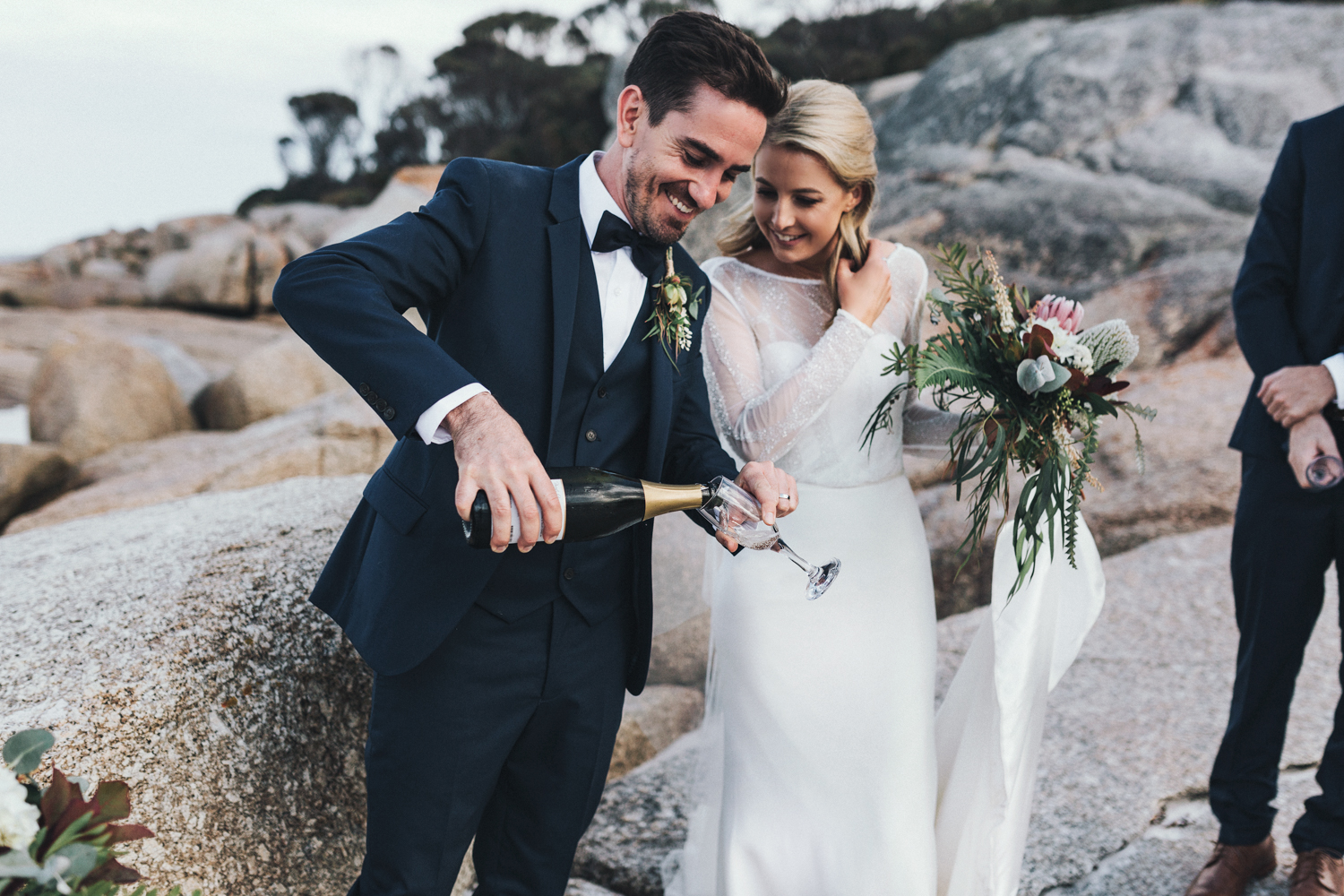 Groom pours champagne for his bride at Bay of Fires Tasmania.