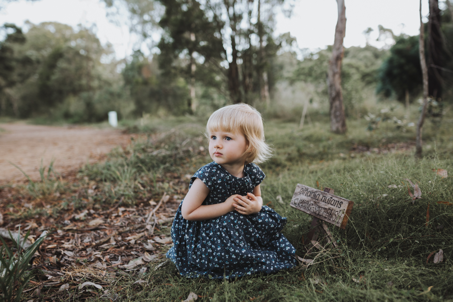 Child sits in nature in vintage dress.