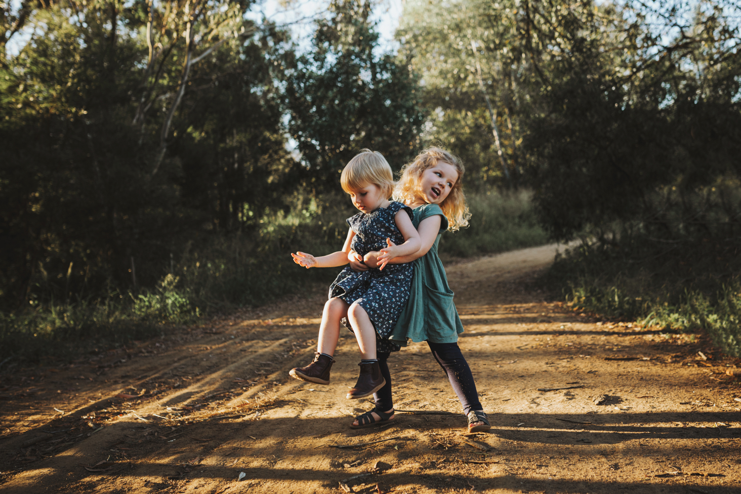Girls play in nature together in beautiful light in Brisbane by