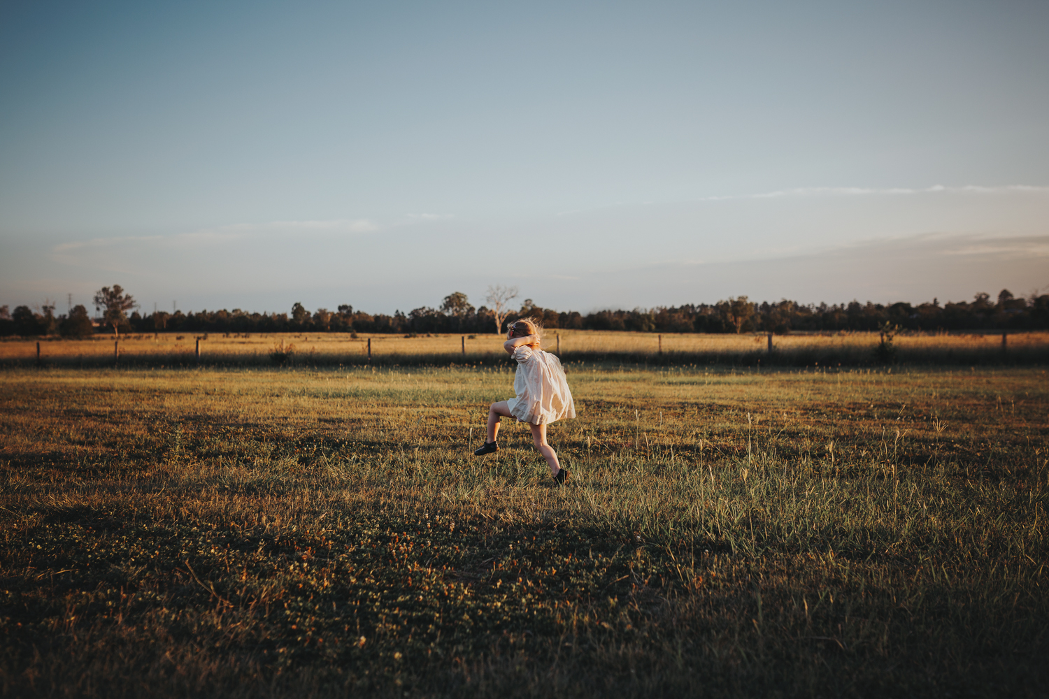 Girl runs through fields during photo shoot with her family.