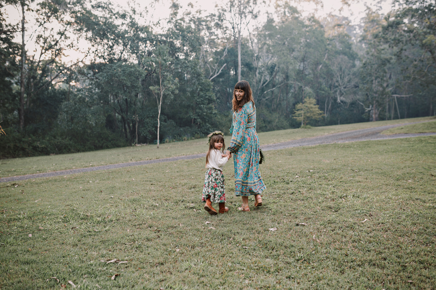 Mother and daughter walk hand in hand during photo session.