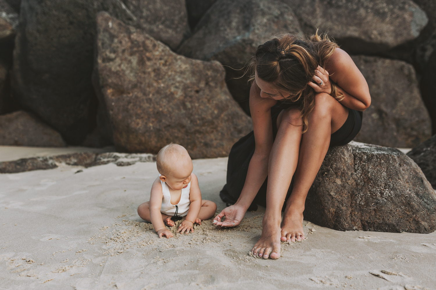 Mother shows baby girl a shell at the beach during beautiful bea
