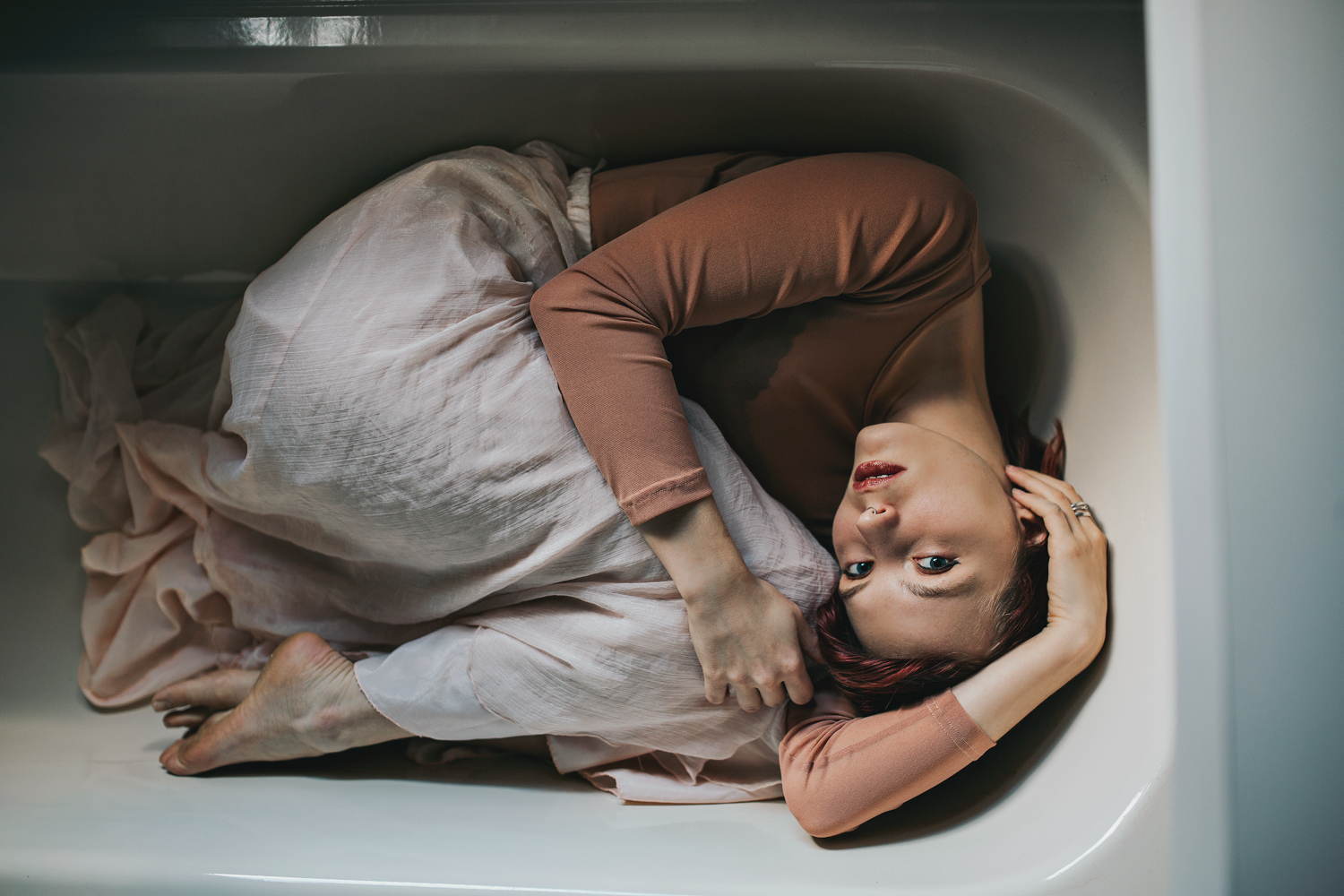 Artistic photo of model huddled in a bath for a fashion photo sh