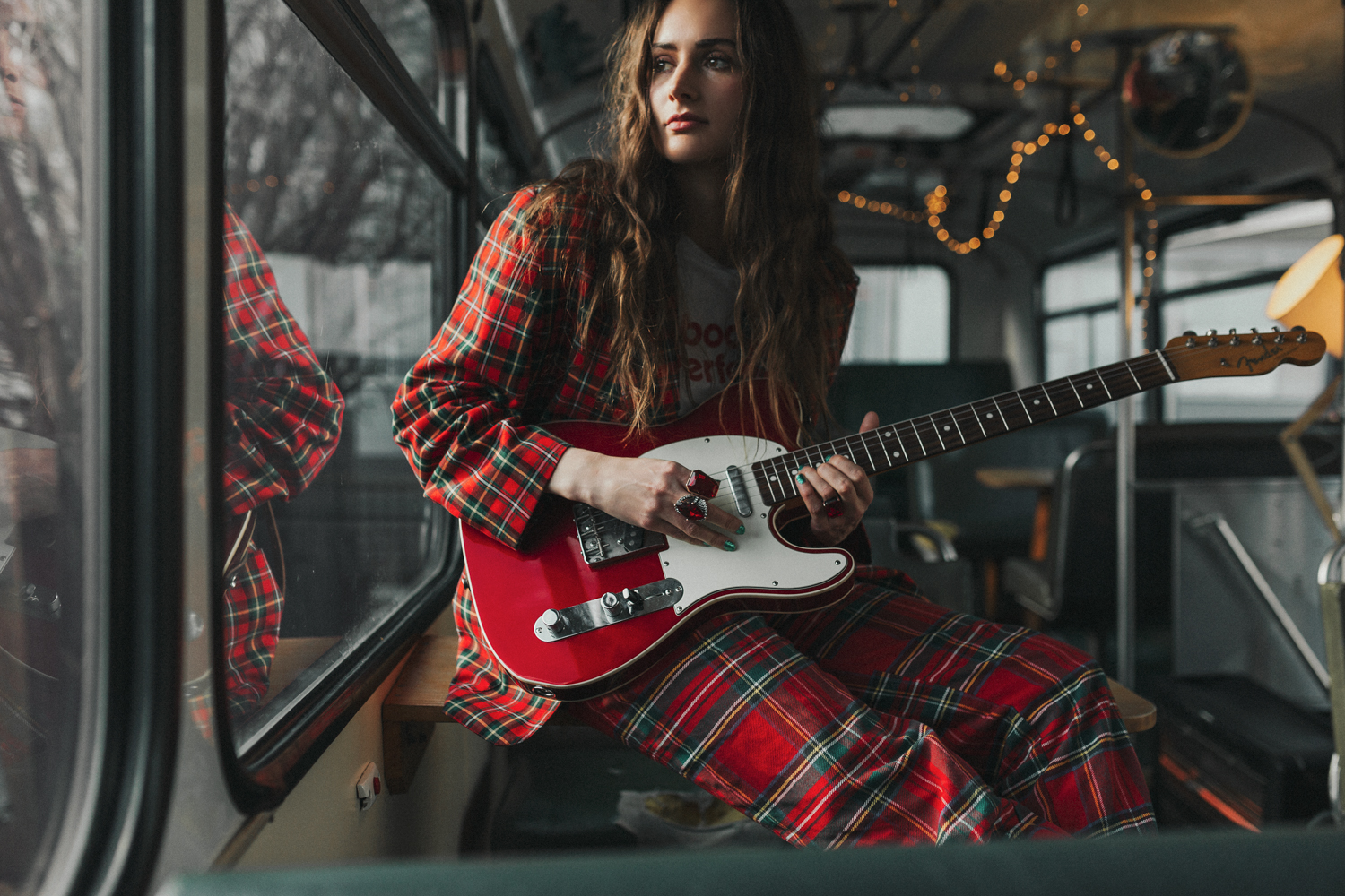 Musician Lasca Dry plays guitar in bus during photo shoot.