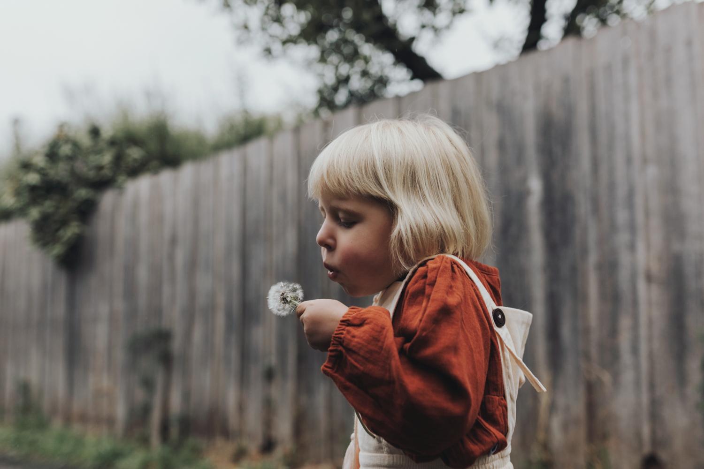 Girl makes wish on dandelion flower in alleyway by Siida Photogr