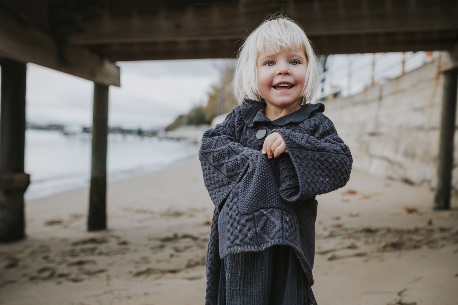 Young girl smiles in knit cardigan in photo for Minouche by Siid
