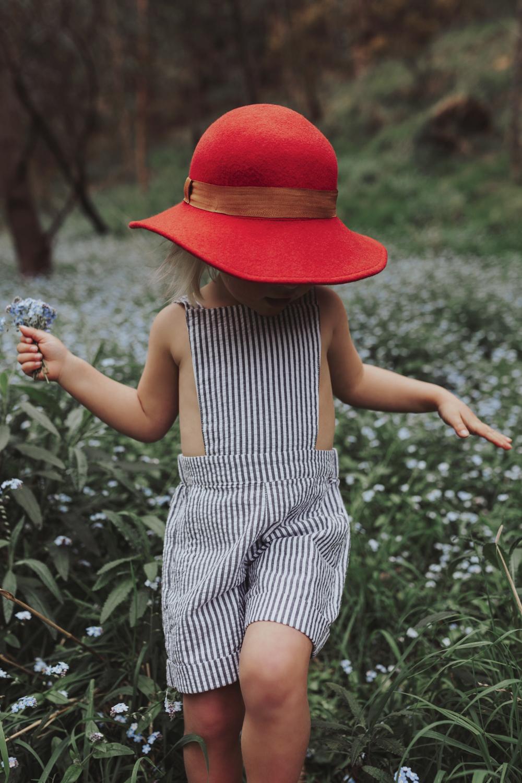 Young girl walks through field of flowers in beautiful photo sho