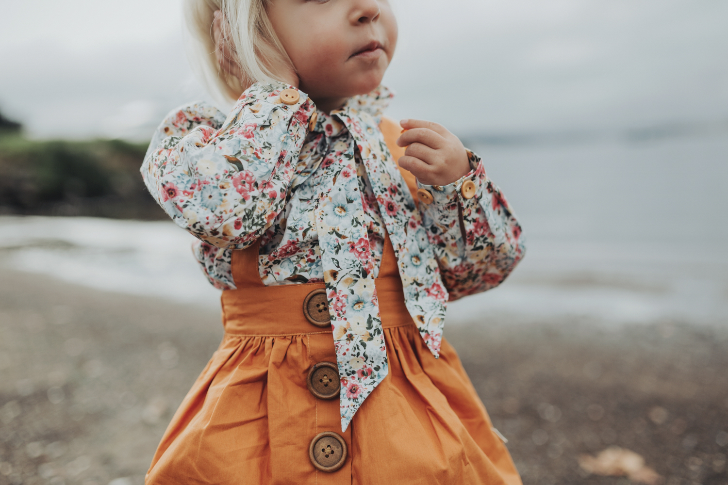 Young girl listens to shells in floral shirt during fashion phot
