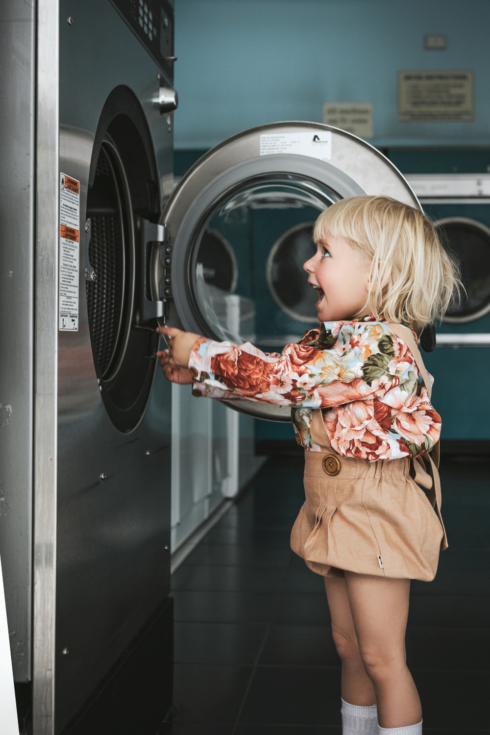 Blonde girl is excited with what's inside a washing machine at l