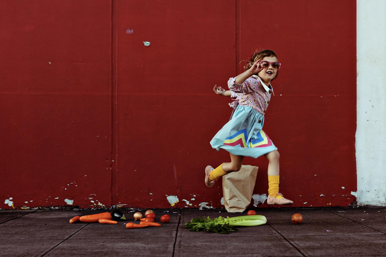 Girl skips over her upturned in vintage kids fashion shoot.