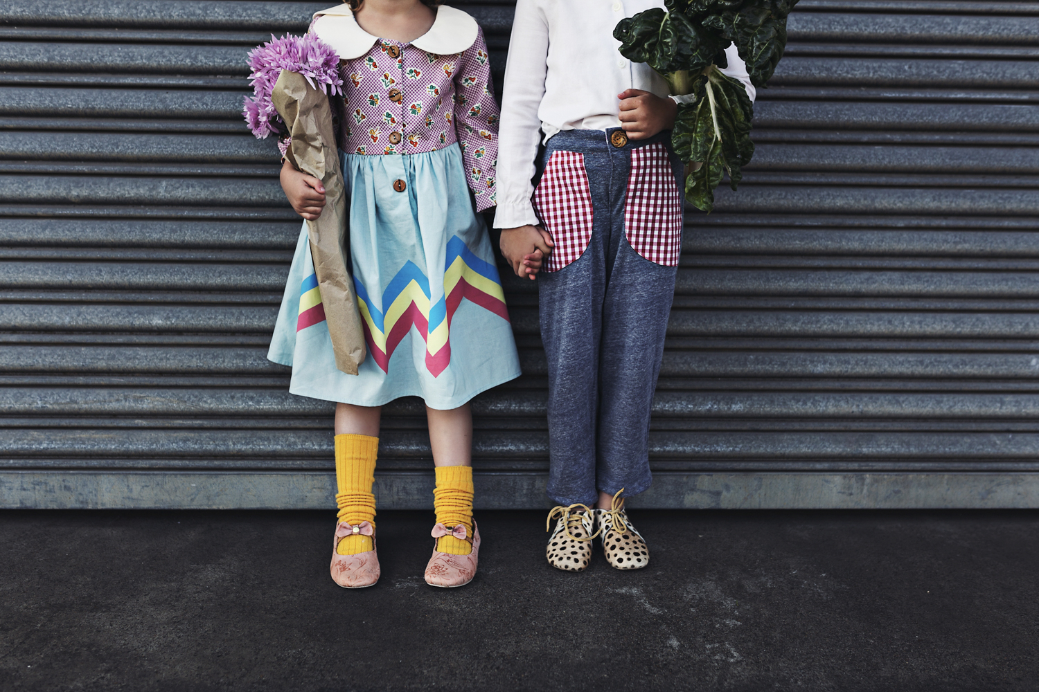Two girls hold hands with their flowers and shopping in cute ret