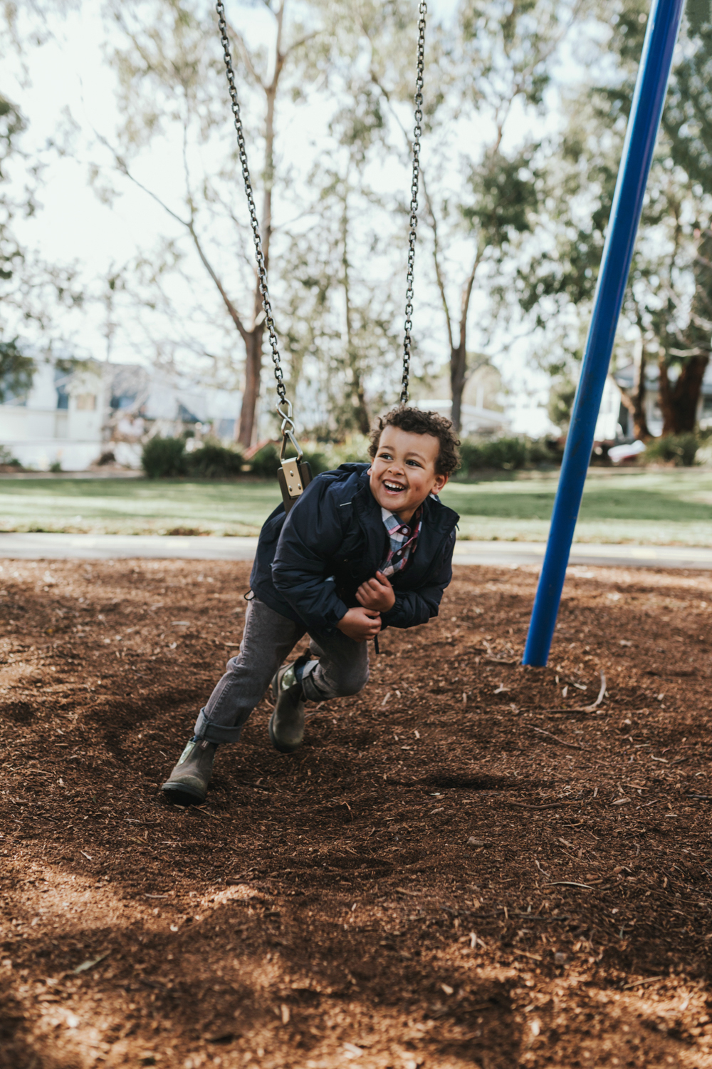 Young boy looks into distance with a big smile wearing Blundstone boots in Tasmanian playground.