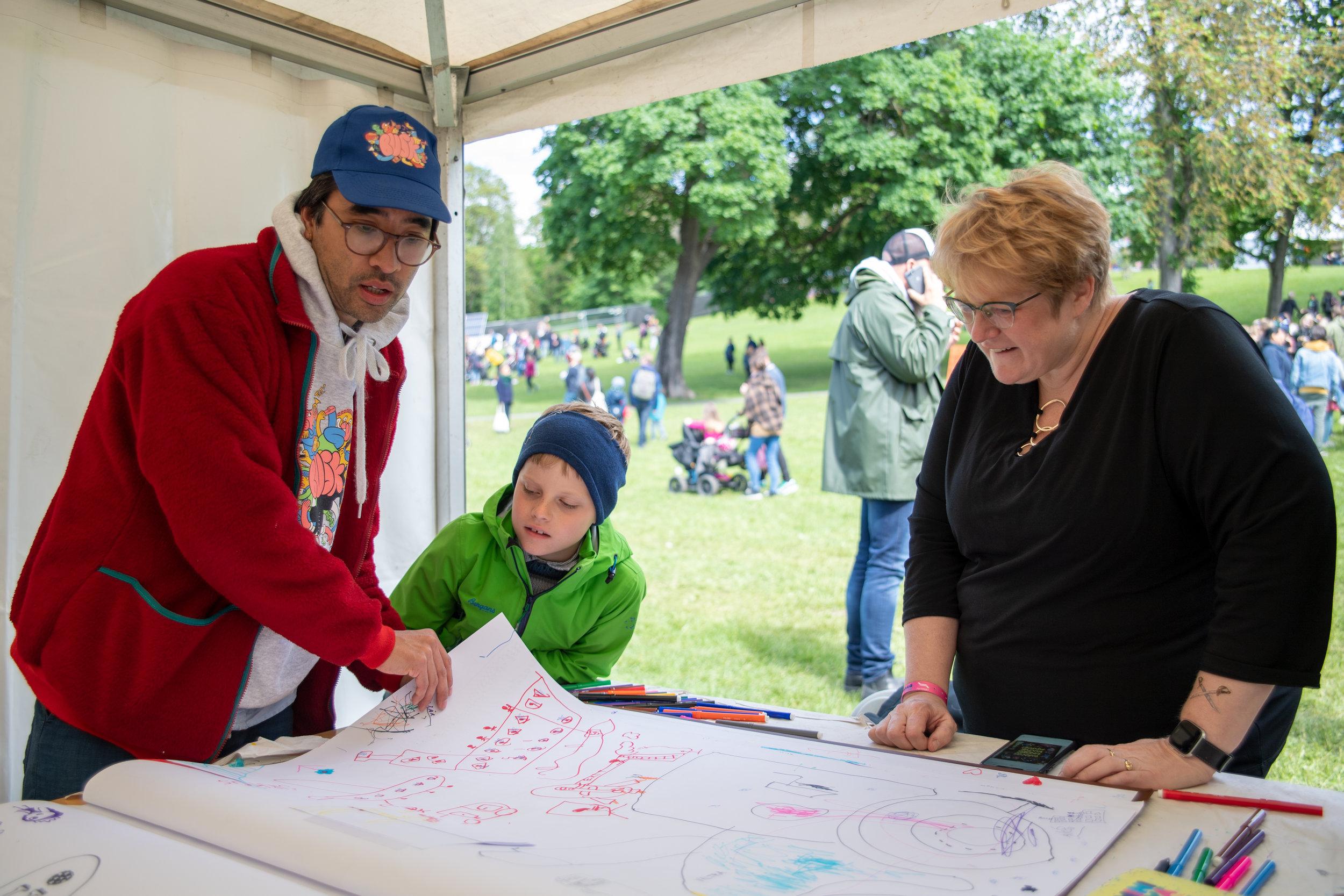 Prosjektleder for BUSK - barn og unges stemmer, kunst og kultur-  viser kulturminister Trine Skei Grande hva barna har skrevet og tegnet i boken på Miniøya