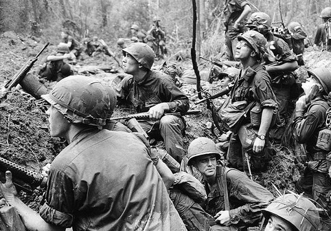 """""""VIETNAM US TROOPS IN 1965—WAR ZONE D"""" BY    MANHHAI,   VIA FLICKR,  CREATIVE COMMONS  (CROPPED): """"AMERICAN INFANTRYMEN CROWD INTO A MUD-FILLED BOMB CRATER AND LOOK UP AT TALL JUNGLE TREES, SEEKING OUT VIET CONG SNIPERS FIRING AT THEM DURING A BATTLE IN PHUOC VINH, NORTHEAST OF SAIGON IN VIETNAM'S WAR ZONE D."""""""