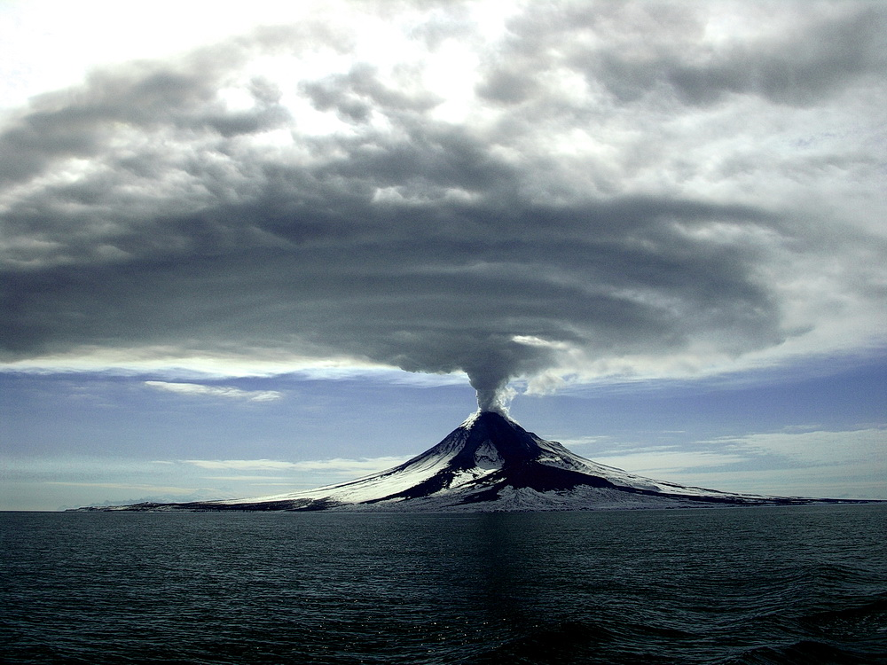 Figure 3: An example of a violent volcanic eruption. This is the Augustine volcanic eruption, 2006. The Augustine Volcano is historically the most active volcano in Alaska's Cook Inlet region. The eruption started on January 11, 2006, and lasted until mid-March of 2006.The cloud above the volcano is mostly volcanic ash. Old ash deposits from this volcano were carried by the winds as far as  3000 km away . Photo By Cyrus Read, U.S. Geological Survey [Public domain or CC0], via Wikimedia Commons.
