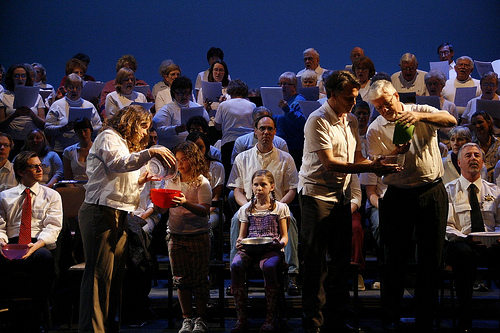 Picture of the choir singing and actors pouring water into each other's bowl.