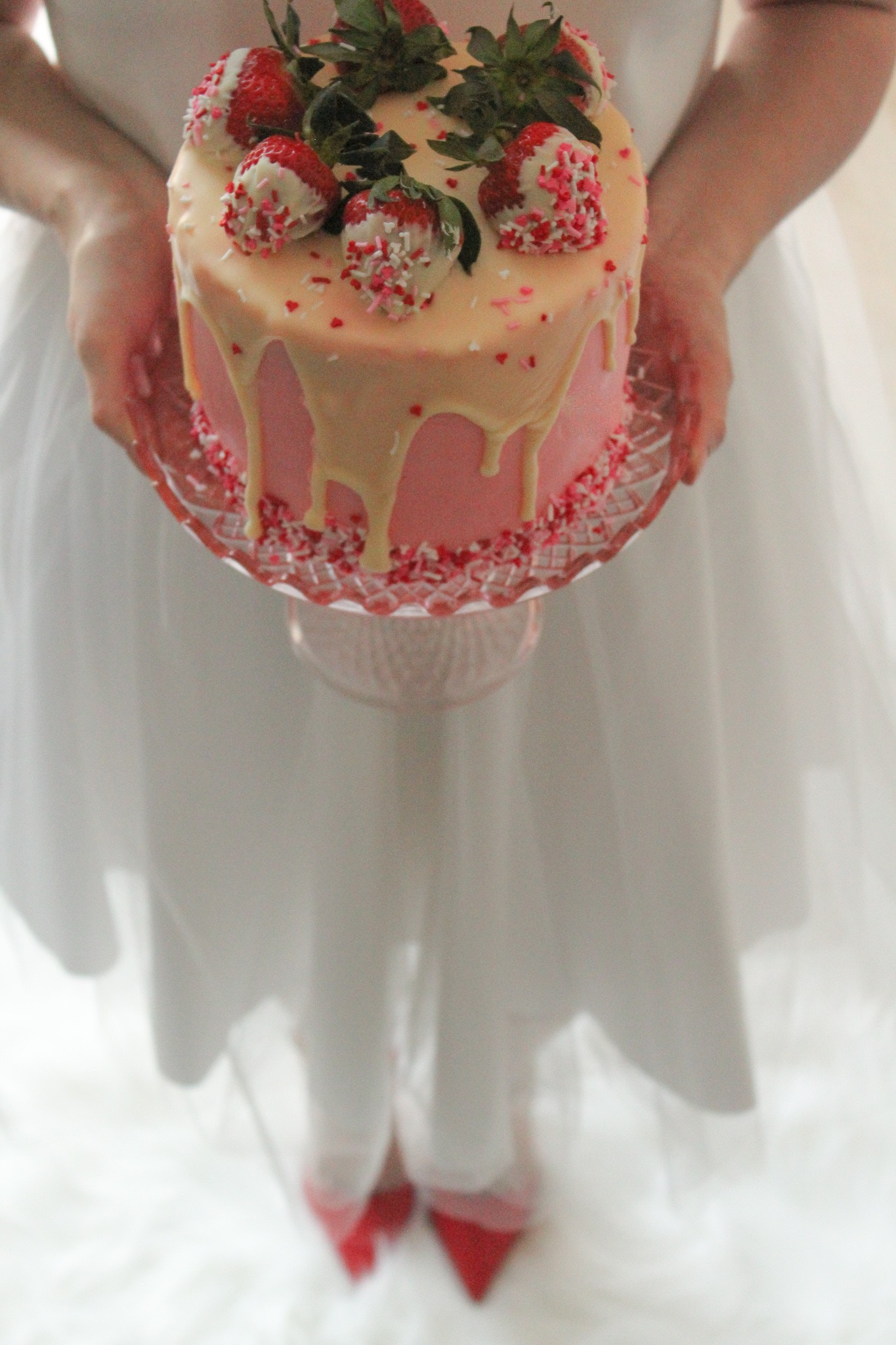 Girl in long white tutu and red heels holding a strawberry champagne cake.