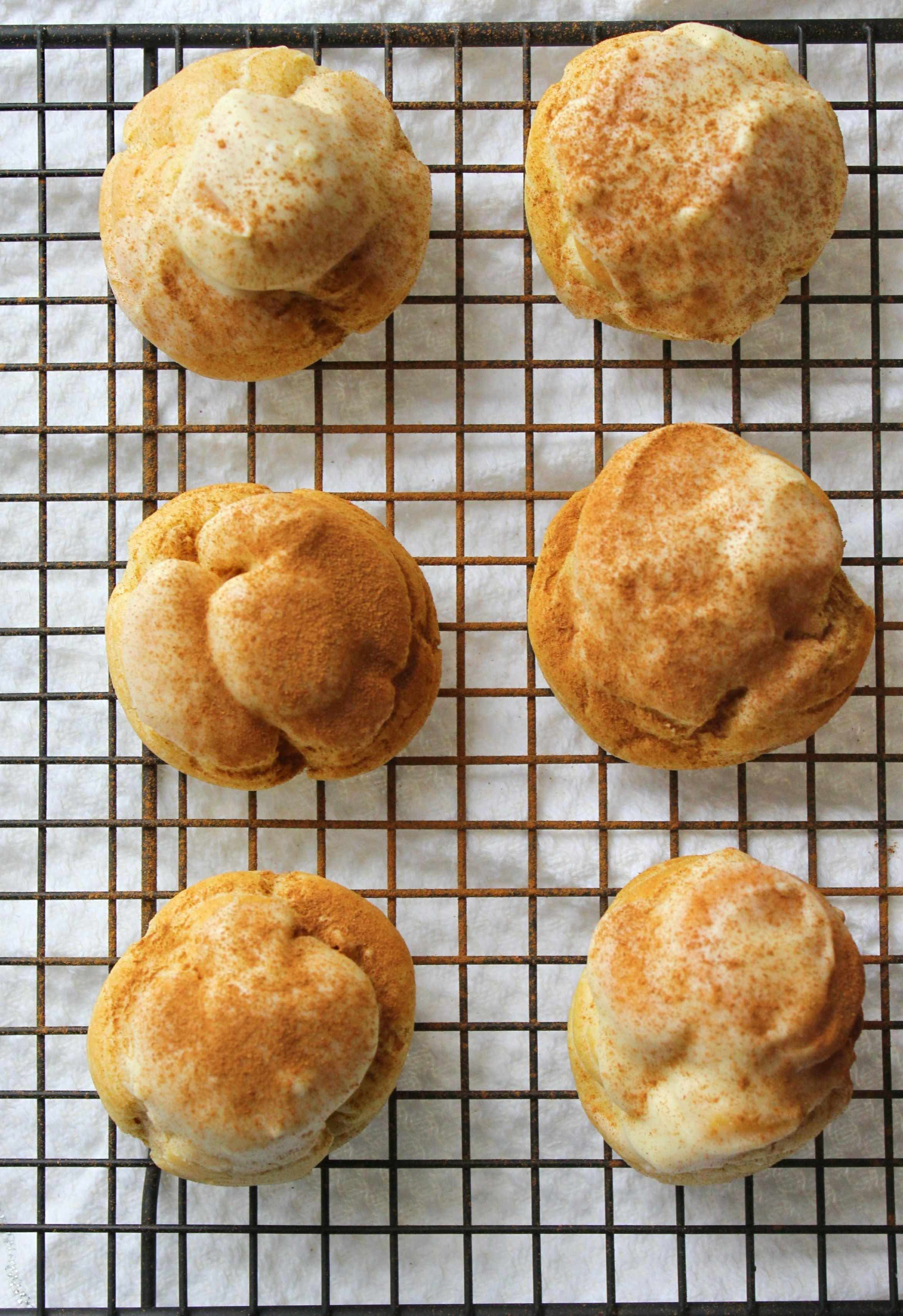 Cream puffs filled with chai whipped cream and topped with white chocolate and cinnamon