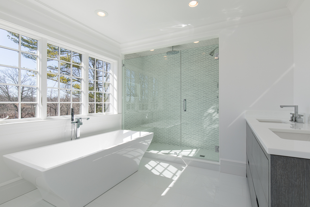 Luxurious Master Bathroom with Soaking Tub, Glass- Enclosed Rain Shower with Bench & Stunning Herringbone Tile Design, Double Vanity, Water Closet & Storage.