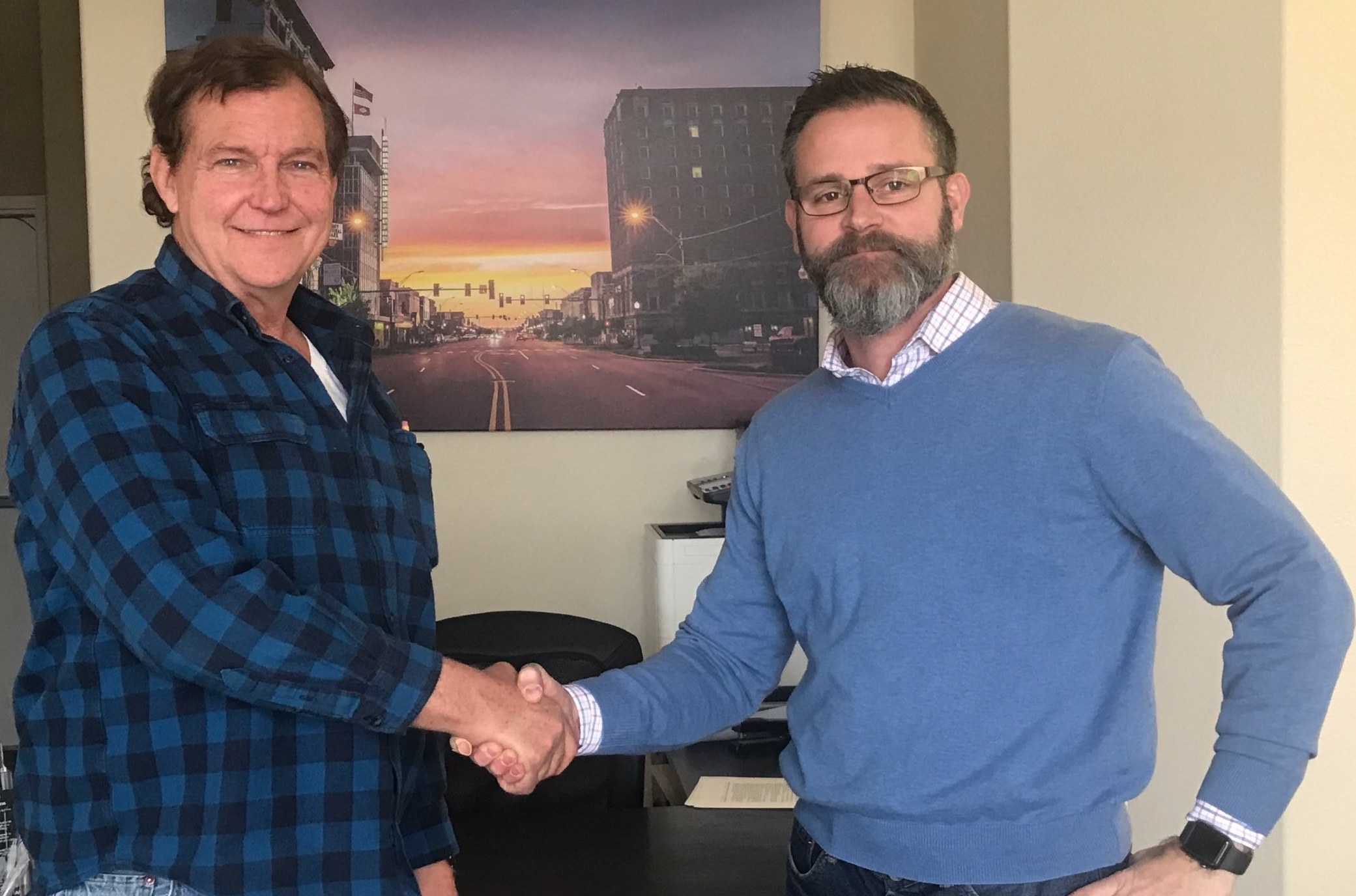 New owner Rick Ralston (R) shakes hands with seller Ed Boyd.
