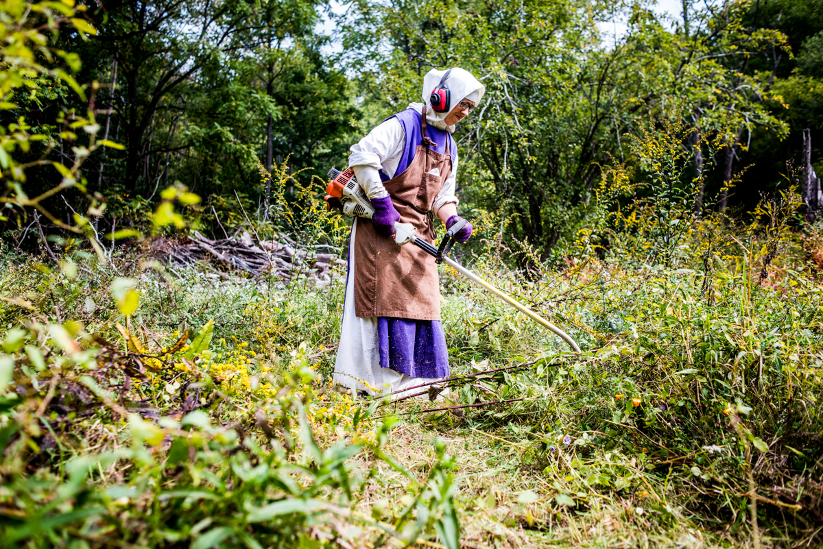 Sister Peggy using a weed trimer to clear a pasture for their cow dawn on their land.