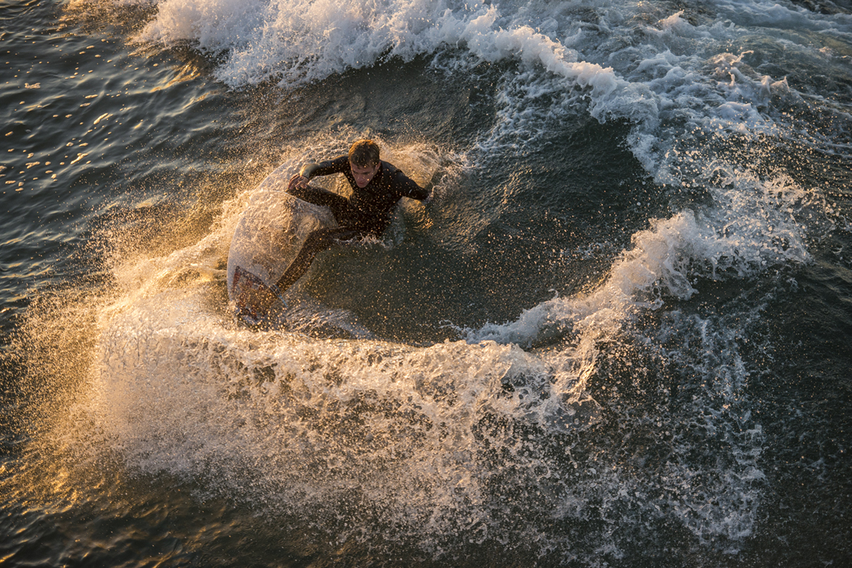 Huntington Beach high school surf team practices and ride waves while the sun rose on November 14, 2016.