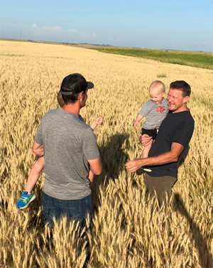 Wheat farmer Tim Raile, right, with his son and grandsons