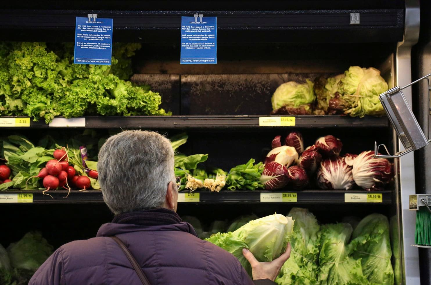 Lisa Dennis selects lettuce from the vegetable shelves at the East End Food Co-op Federal Credit Union in Pittsburgh on Nov. 20. (Jessie Wardarski/Pittsburgh Post-Gazette/AP)