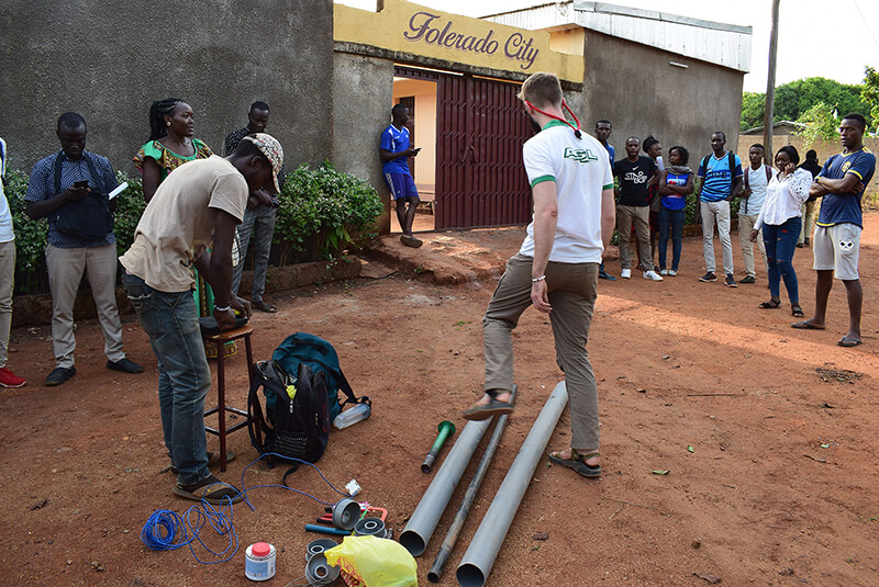 Scott Massey, founder of Heliponix, steps over some pipes at the beginning of a hydroponic farm workshop at the University of Ngaoundéré in Cameroon. Massey, a Purdue University graduate, traveled to Cameroon to teach people about hydroponics and entrepreneurship. He is the co-founder of Heliponix, which makes the GroPod, an innovative appliance that fits under a kitchen counter and grows produce year-round. (Photo provided)     Download image