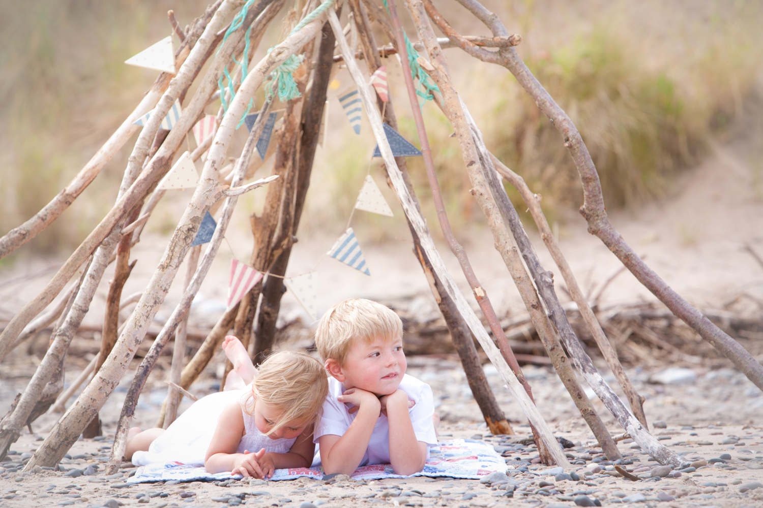 Siblings chilling and relaxed on the beach under a stick den with bunting