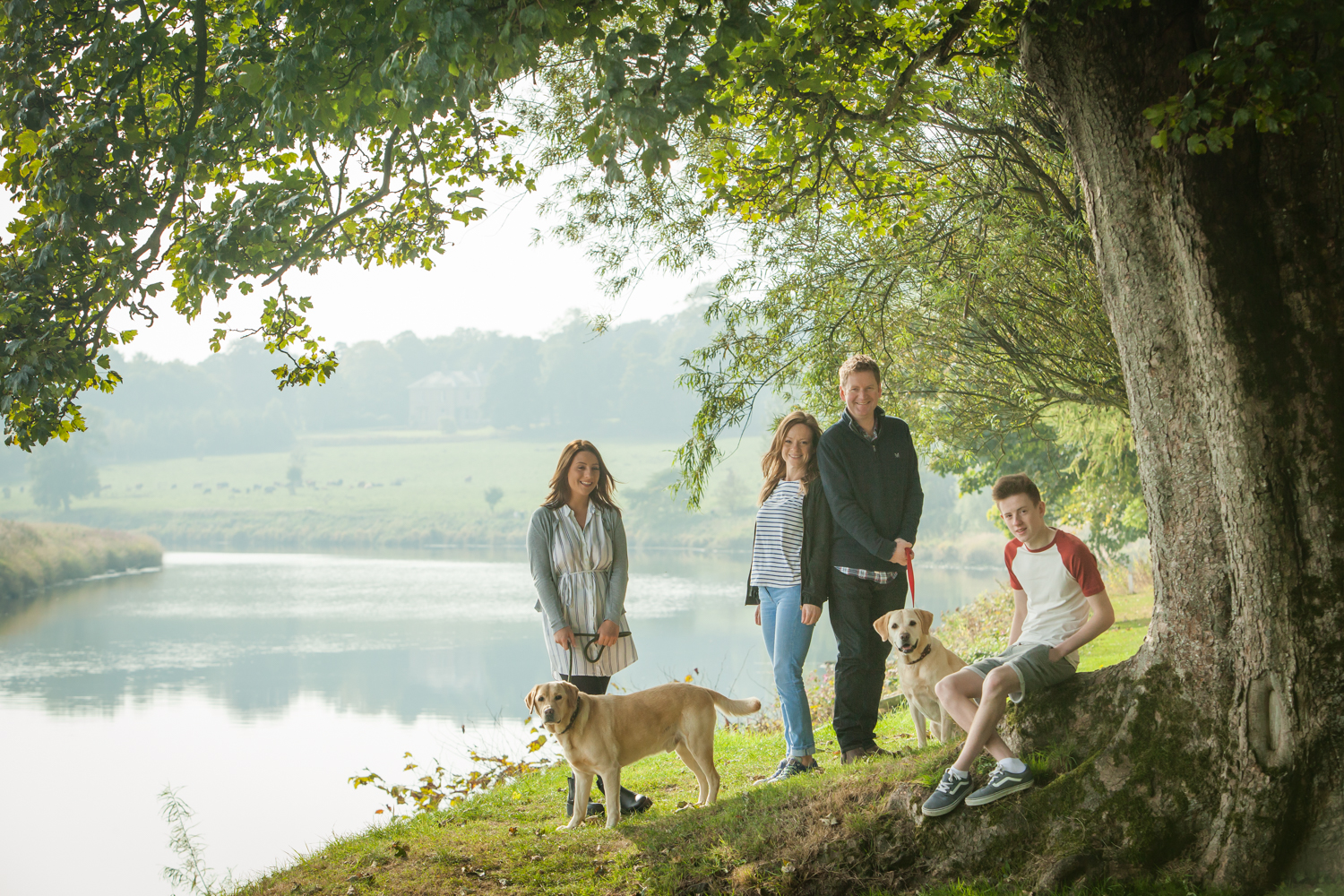 family with dogs at riverside