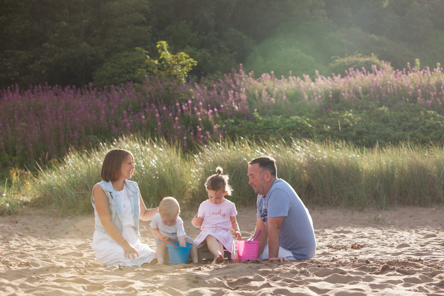 Family at sundown on the beach, styled in pastel clothing
